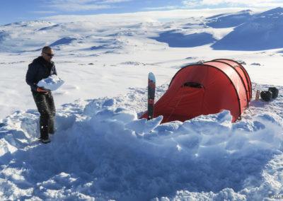 construction d'un mur en neige pour protéger la tente du vent
